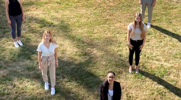 MRH Trowe Auszubildende 2020. Fünf Auszubildende von oben auf einer Wiese.